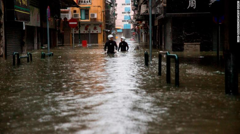 Rescue workers wade through floodwaters during a rescue operation in Macau on Sunday, September 16.