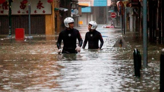 Rescue workers wade through floodwaters during a rescue operation in Macau on September 16.