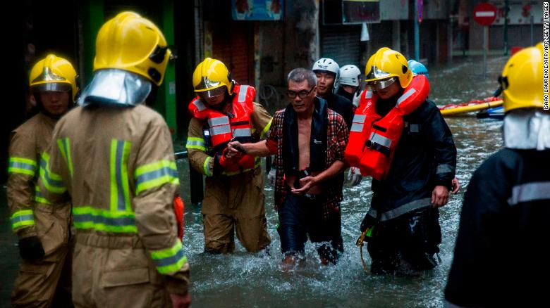 A shop owner is rescued by members of the fire brigade from a flooded area of Macau on Sunday.
