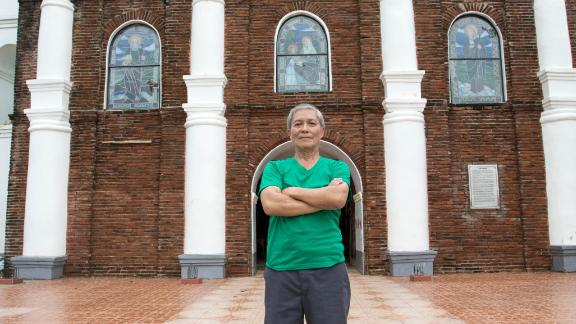 Arthur Pagador, 68, stands in front of Buguey's church.