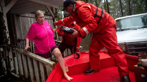 Coast Guard member Blake Gwinn helps Josephine Horne escape her flooded home in Columbus County, North Carolina, on September 16.