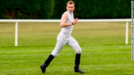 Jockey Ryan Moore races across the track after arriving from Doncaster Racecourse by helicopter.