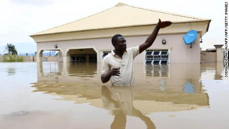 A man gestures next to his flooded house following heavy rain near the Nigerian town of Lokoja, in Kogi State, on September 14, 2018.