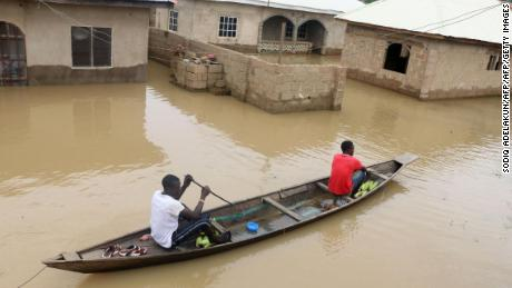 Residents steer a dugout canoe past flooded houses in Lokoja capital of Kogi State on September 14, 2018.