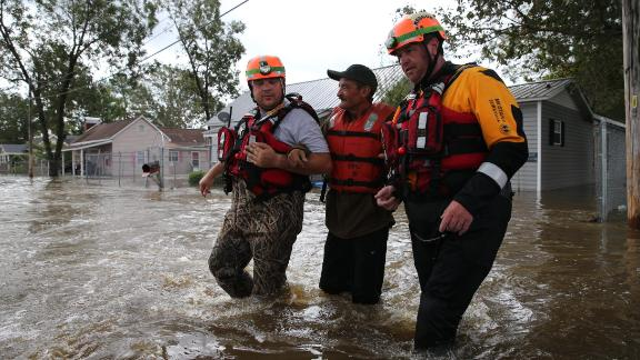 Lumberton Fire and Rescue members help a resident through floodwaters on Monday.