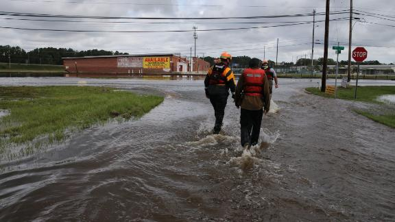 Lumberton North Carolina Fire and Rescue members help a resident walk through flooded waters in Lumberton, North Carolina on September 17, 2018. - Catastrophic floods raised the threat of landslides and dam failures across the southeastern United States on Monday, prolonging the agony caused by a killer hurricane that has left more than a dozen people dead and caused billions of dollars in damage. Downgraded to a tropical depression, Florence crept over South and North Carolina, dumping heavy rains on already flood-swollen river basins that authorities warned could bring more death and destruction. (Photo by Alex EDELMAN / AFP)       (Photo by Alex Edelman/Getty Images)