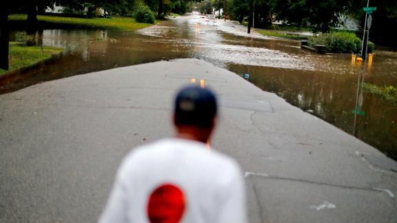 Helen McKoy walks down a flooded street in her neighborhood in Fayetteville on Sunday.