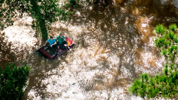 Two people near Wallace, South Carolina, sit on the top of a vehicle that was caught in flooding on Monday, September 17.