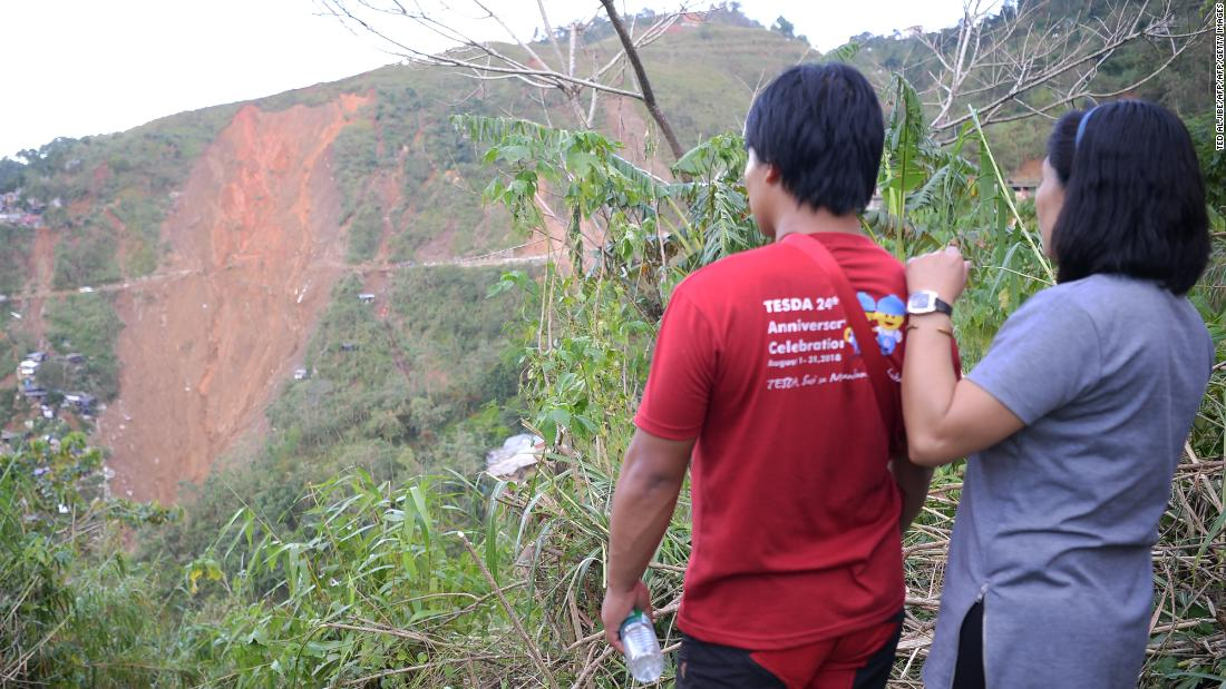Philippines typhoon: Families line up to identify landslide dead