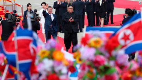 South Korean President Moon Jae-in, center left, waves as North Korean leader Kim Jong Un, center right, applauds upon Moon's arrival at Sunan International Airport in Pyongyang Tuesday.