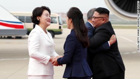 Moon Jae-in and Kim Jong Un hug as their wives shake hands.