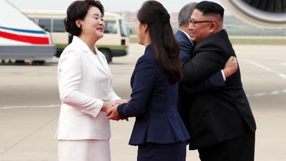 Moon Jae-in and Kim Jong Un hug as their wives shake hands.