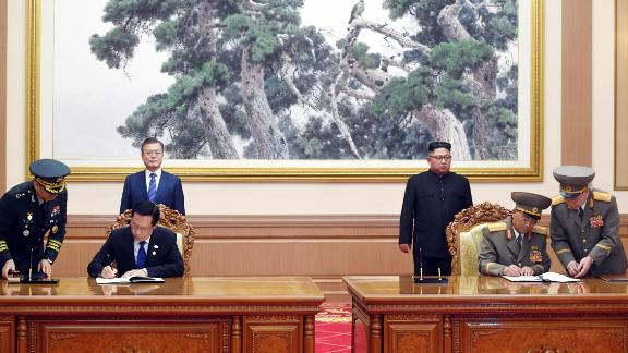 "South Korean Defense Minister Song Young-moo, second from left, and his North Korean counterpart No Kwang Chol sign a military agreement, vowing to ""cease all hostile acts against each other."""