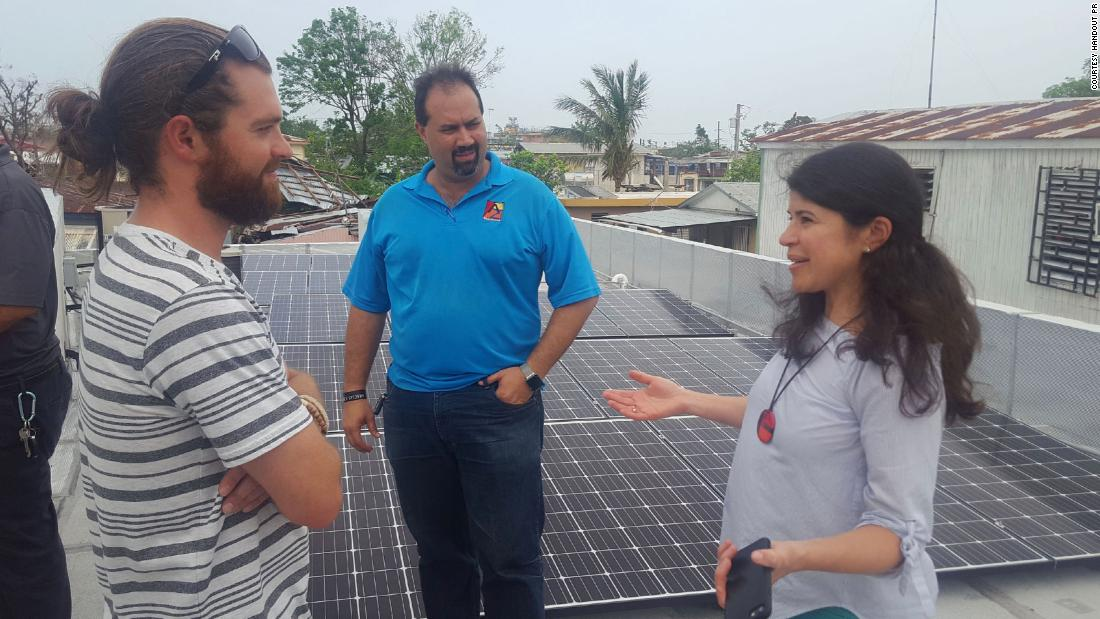 Resilient Power PR co-founder Cristina Roig-Morris in San Juan, working with a team installing solar panels over a community center.