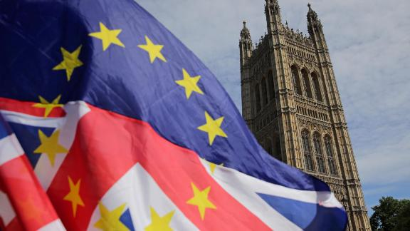Pro-EU demonstrators wave an mixed EU and Union flag as they protest against Brexit, outside of the Houses of Parliament in central London on June 11, 2018. - After a rollercoaster week of Brexit rows within her government and with Brussels, British Prime Minister Theresa May will on Tuesday seek to avoid another setback in a long-awaited showdown with parliament. MPs in the House of Commons will vote on a string of amendments to a key piece of Brexit legislation that could force the government