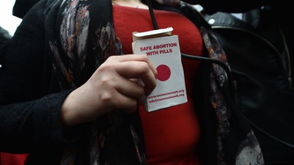 BELFAST, NORTHERN IRELAND - MAY 31: An unidentified woman displays an abortion pill packet after taking one of the pills as abortion rights campaign group ROSA, Reproductive Rights Against Oppression, Sexism and Austerity distribute abortion pills from a touring bus on May 31, 2018 in Belfast, Northern Ireland. Flouting Northern Irish governmental laws which forbid the use of abortion pills the group are also protesting outside offices belonging to the main political parties in the province. Women in Northern Ireland have been prosecuted for buying abortion pills over the internet and it is illegal for a woman to have an abortion unless in special circumstances unlike the rest of the United Kingdom. The Republic of Ireland voted in favour of pro-choice last week in a referendum. (Photo by Charles McQuillan/Getty Images)