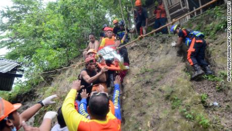 Rescuers carry a resident brought out from the landslide site.