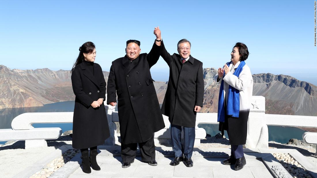 The leaders of North and South Korea join hands Thursday, September 20, atop North Korea's Mount Paektu. From left are North Korean first lady Ri Sol Ju, North Korean leader Kim Jong Un, South Korean President Moon Jae-in and South Korean first lady Kim Jung-sook.