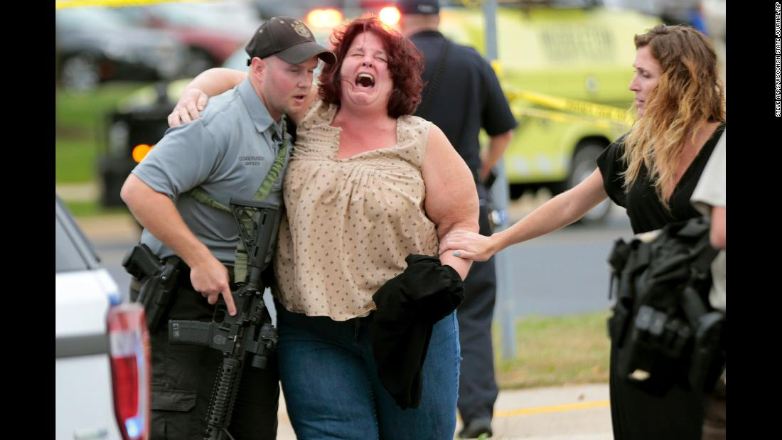 A woman is escorted from the scene of a shooting in Middleton, Wisconsin, on Wednesday, September 19. Three people were seriously wounded when a co-worker opened fire at a software firm, police said.