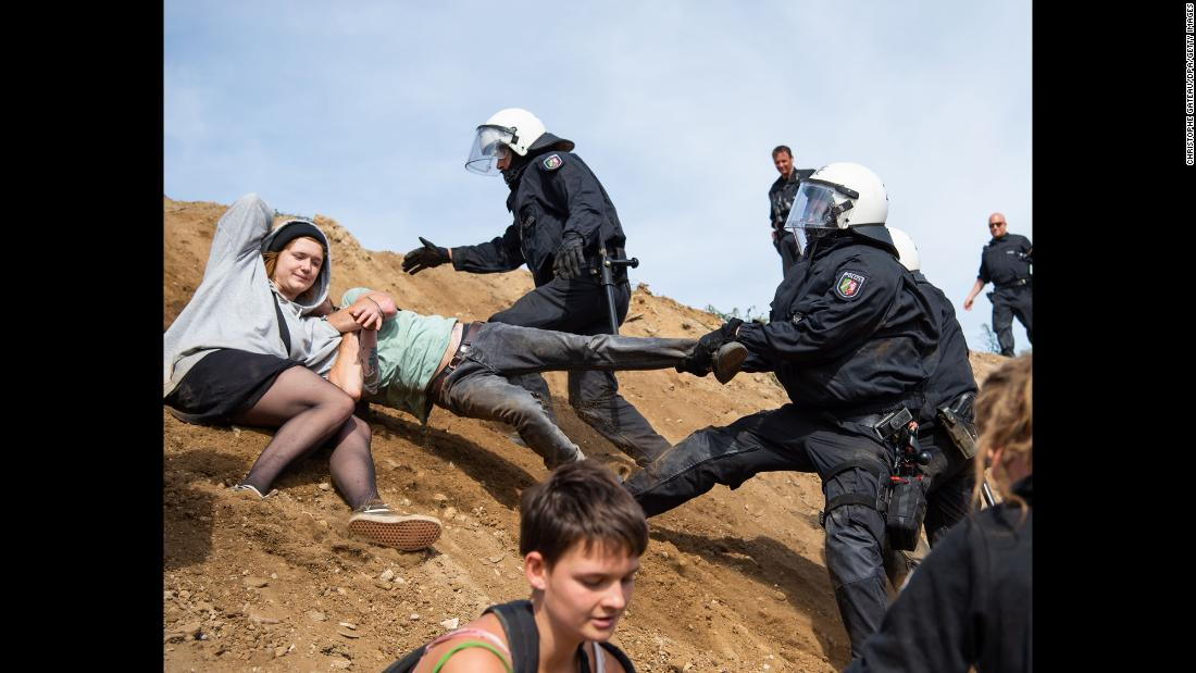 Police grab a protester's leg as they try to clear Germany's Hambach Forest on Sunday, September 16. Activists have been holed up in treehouses to prevent an energy company from razing more of the forest and mining coal.