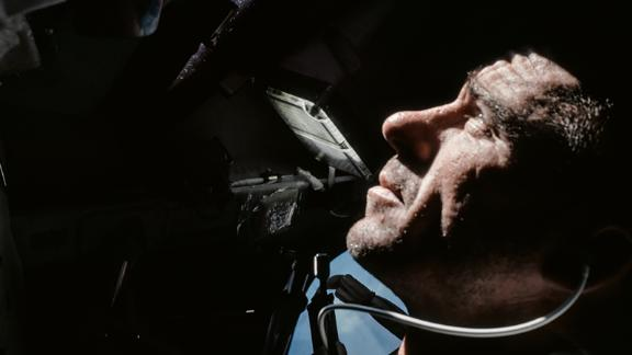Astronaut Walt Cunningham looks out of the Command Module window during Apollo 7's 11-day orbit around the Earth.