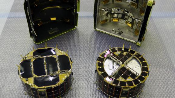 The small rovers, MINERVA-II1. Rover-1A is on the left and Rover-1B is on the right. Behind the rovers is the cover in which they are stored.