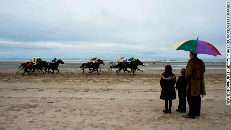 LAYTOWN, IRELAND - SEPTEMBER 08: Racegoers shelter from the rain as the runners pass during the Laytown race meeting run on the beach on September 08, 2011 in Laytown, Ireland. (Photo by Alan Crowhurst/Getty Images)