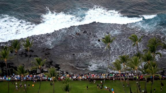 Spectators sit on a rock wall during the Ironman World Championship on October 14, 2017.