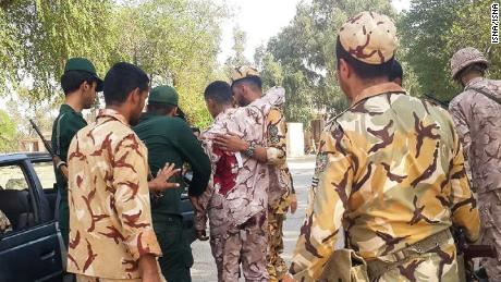 A soldier wounded in the attack is treated at the scene in the southern Iranian city of Ahvaz.