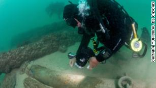 Maritime archaeologists explore the shipwreck.