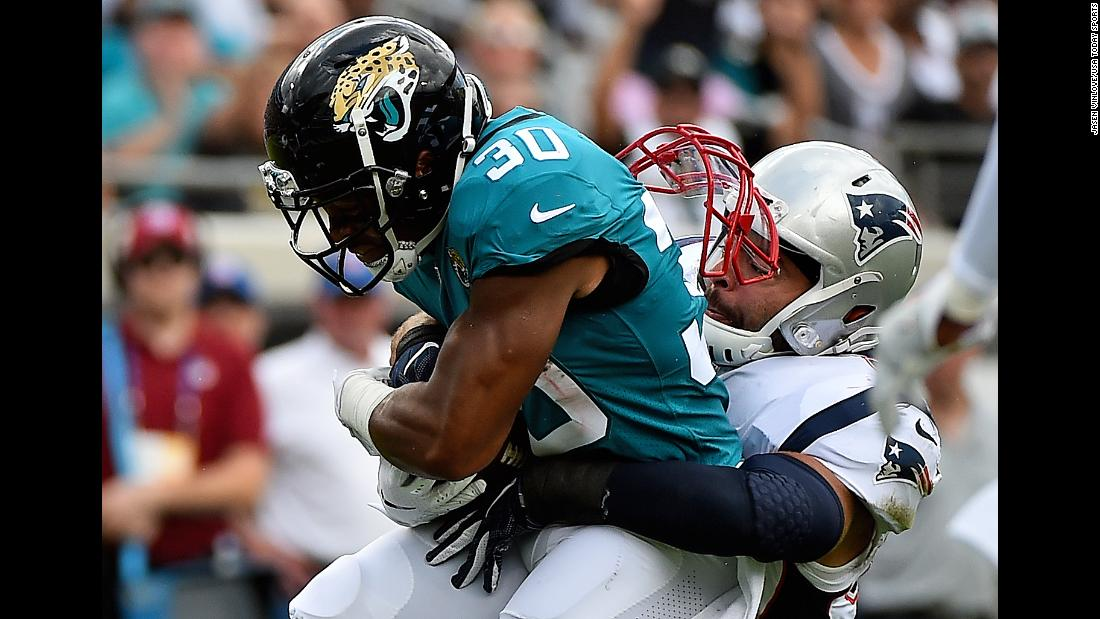 New England Patriots linebacker Kyle Van Noy's face mask comes undone as he tackles Jacksonville Jaguars running back Corey Grant on Sunday, September 16, in Jacksonville, Florida.