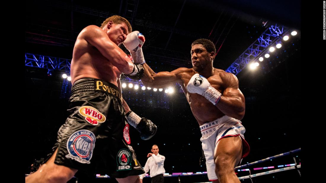 Anthony Joshua and Alexander Povetkin trade punches during the IBF, WBA Super, WBO & IBO World Heavyweight Championship title fight on Saturday, September 22, in London.