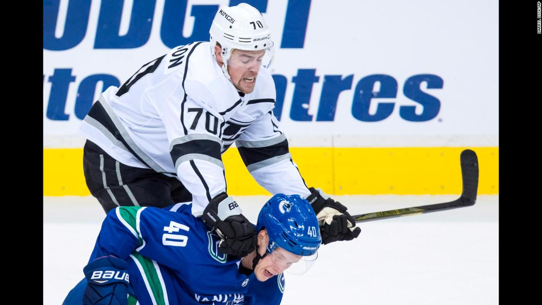 Tanner Pearson of the Los Angeles Kings checks Elias Pettersson of the Vancouver Canucks during the first period of an NHL hockey preseason game Thursday, September 20, in Vancouver, British Columbia.