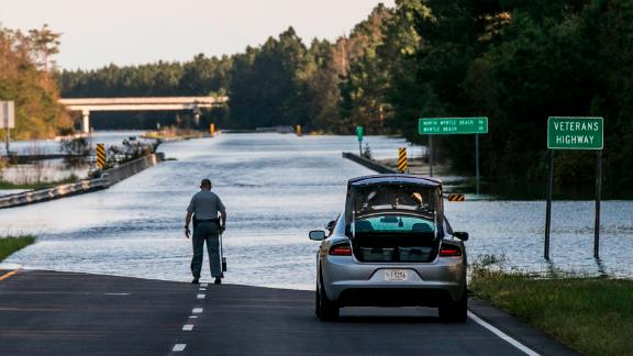 An officer with the South Carolina State Highway Patrol marks the water level of Highway 22 on Saturday.