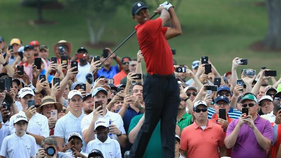 Fans take pictures as Woods tees off on the fourth hole Sunday. Thousands of fans followed Woods during the final round.