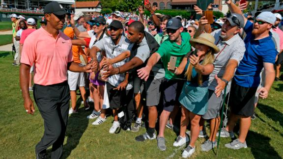 Tiger Woods fist-bumps with fans after leaving the 18th hole during the first round on Thursday, September 20.