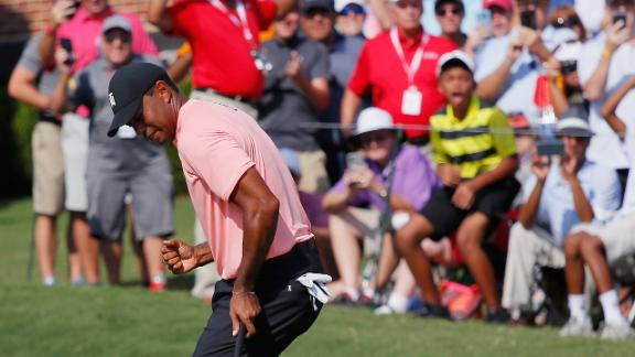 Woods celebrates after making an eagle putt on 18 on Thursday during the first round.