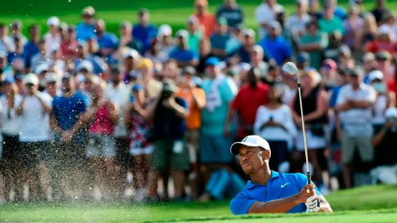 Woods shoots out of the sand onto the 15th green Saturday during the third round.