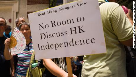 "A member of pro-government group 'Real Hong Kong's View' holds a placard that reads ""No Room to Discuss HK Independence"" during a protest outside the Foreign Correspondents' Club in Hong Kong on August 8, 2018."