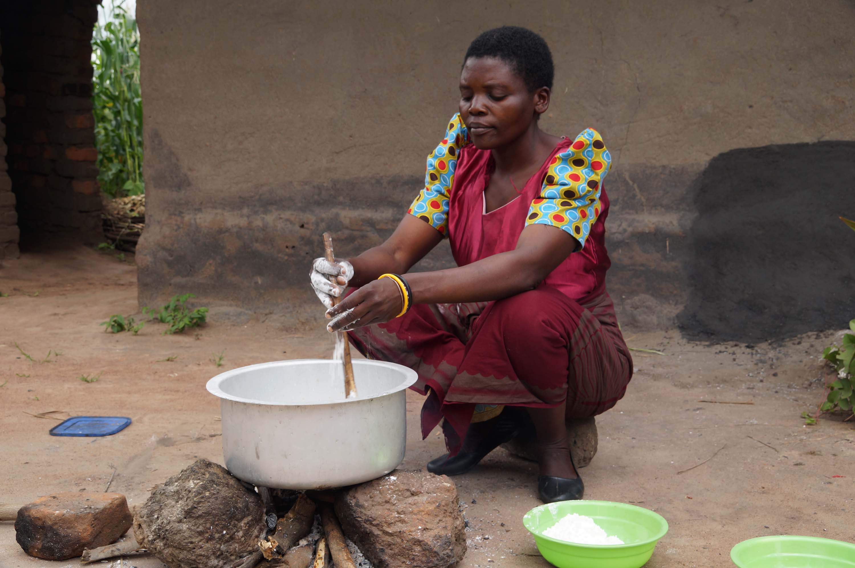 Margret Kawala preparing porridge at her home.
