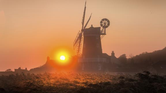 Cley next the Sea, England: The 18th-century Cley Windmill is lit dramatically at sunrise on the Norfolk coast in England