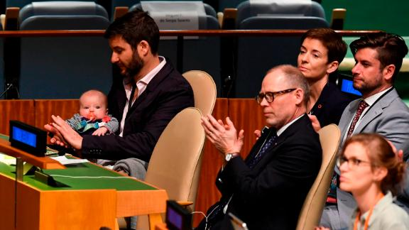 Clarke Gayford (C) claps while holding his daughter Neve Te Aroha Ardern Gayford.