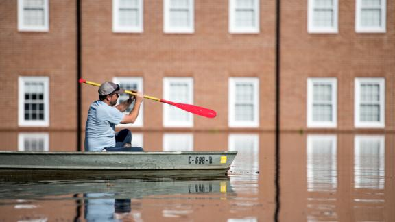Taylor James navigates floodwaters in a boat in front of Trinity United Methodist Church in Conway, South Carolina on Wednesday, September 26.