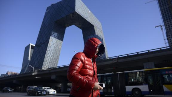 A man walks down the street as the iconic CCTV headquarters loom in the background in the central business district of Beijing on January 20, 2017.