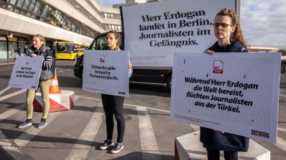 Demonstrators hold signs calling for freedom of the press in Turkey during a protest outside Tegel airport in Berlin on Thursday.