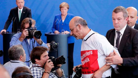 Journalist Adil Yigit is taken away as Turkish President Recep Tayyip Erdogan and German Chancellor Angela Merkel give a joint news conference in Berlin on Friday.