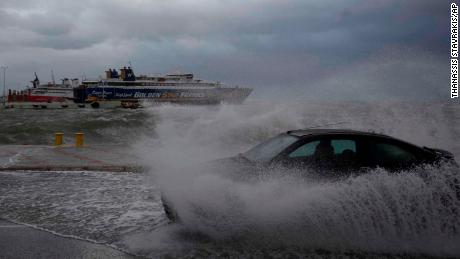 A car drives through seawater from crashing waves on the road during bad weather at the port of Rafina, east of Athens, on Thursday, Sept. 27
