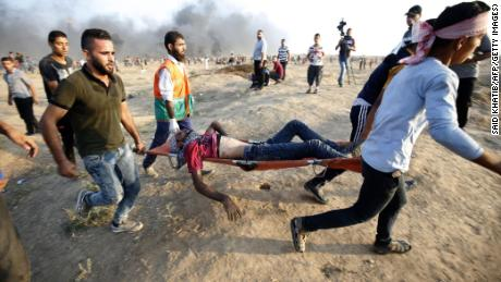 Protesters carry an injured Palestinian during clashes Friday on the Israeli border fence east of Gaza City.