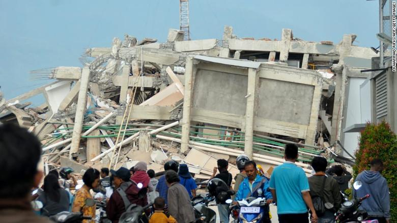 Residents gather to look at a collapsed building in the aftermath of the quake and tsunami in Palu on September 29.