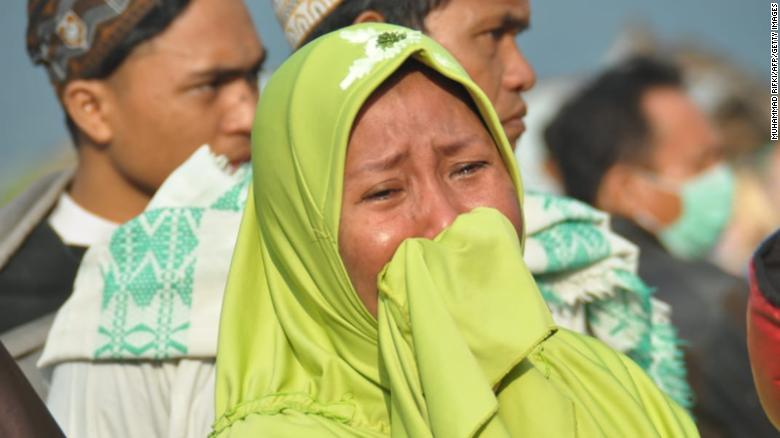 A woman cries as people survey the damage in Palu on September 29.